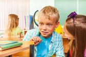 Espantado o rapaz se senta na mesa — Fotografia Stock