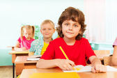 Cute boy looking straight and writing — Stock Photo
