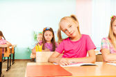 Smiling girl sits at desk — Stock Photo