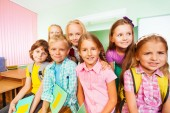 Schoolchildren sitting near desk — Stock Photo