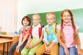 Schoolchildren sitting near desk — Stock Photo