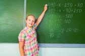 Girl writing mathematics equation — Zdjęcie stockowe