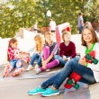 Girl with skateboard and friends — Stock Photo #60955291
