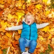 Blond boy laying on autumn leaves — Stock Photo #60955709