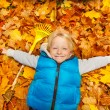 Blond boy laying on autumn leaves — Stock Photo #60955713