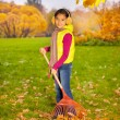 Asian girl with big red rake — Stock Photo #60956201