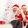 Family opening presents under Christmas tree — Stock Photo #60956435