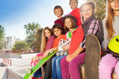 Friends sitting with skateboards — Stock Photo