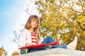 Blond girl with long hair with skateboard — Stock Photo