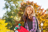 Serious looking girl with skateboard — Stock Photo