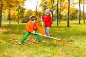 Boy and girl with cleaning grass — Stock Photo