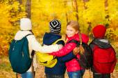 Kids group standing close with rucksacks — Stock Photo