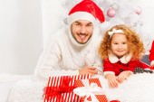 Father with daughter under Christmas tree — Stock Photo