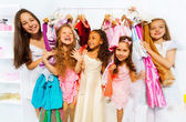 Happy girls among clothes — Stock Photo