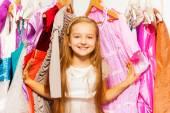 Girl standing between hangers — Stock Photo