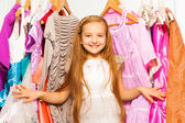 Girl standing among dresses — Stock Photo