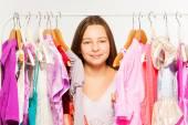 Girl  between hangers with dresses — Stock Photo