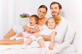 Parents on bed with children — Stock Photo