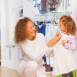Mother trying dress on her daughter — Stock Photo #65977805