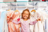 Girl standing between clothes — Stock Photo