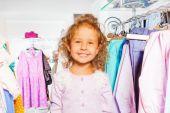 Roztomilá dívka mezi oblečení — Stock fotografie
