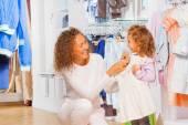 母亲试图对她女儿的衣服 — 图库照片