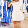 Girl holding and trying dress on hanger — Stock Photo #65983737