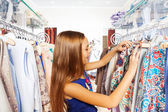 Girl searching for clothes during shopping — Stock Photo