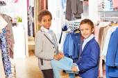 Boys in suits hold clothing at shop — Foto de Stock