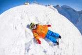 Boy in mask laying on snow — Stock Photo