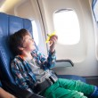 Boy with toy plane sits  by airplane window — Stock Photo #66044525