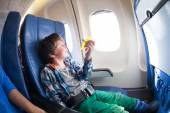 Boy with toy plane sits  by airplane window — Стоковое фото