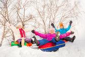 Excited children sliding down on tubes — Stock Photo