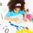 Concentrated African girl writes letters — Stock Photo #77371702