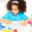 African girl writing letters with pencil — Stock Photo #77371704