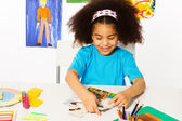 African girl putting puzzle pieces — Stock Photo