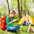 Boy with backpack writes notebook at camping — Stock Photo #77383402