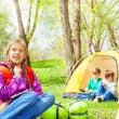 Looking girl with backpack rests in camp — Stock Photo #77383422