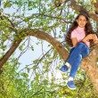 Girl sitting on branch of tree — Stock Photo #77383606