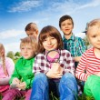 Cute children sitting on grass with magnifiers — Stock Photo #77387384