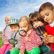 Children sitting in field with magnifiers — Stock Photo #77387386