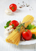 Pasta spaghetti, cheese, vegetables and spices on a white wooden table. — Foto de Stock