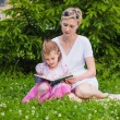 Little girl and her mother reading a book — Stock Photo #68458477