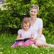 Little girl and her mother reading a book — Stock Photo #68458557