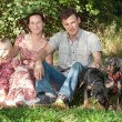 The family sits on a grass in park, nearby there are two dogs. — Stock Photo #52172563