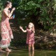 Mother plays in the daughter, starting up soap bubbles — Stock Photo #52354233