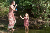 Mother plays in the daughter, starting up soap bubbles — Stock Photo