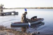 The hunter with a dog in an inflatable boat sail on hunting — Stock Photo