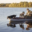 The hunter floats in the boat with two dogs — Stock Photo #58879795