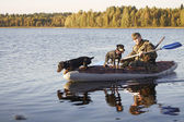 The hunter floats in the boat with two dogs — Stock Photo
